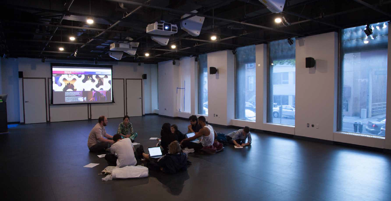 Image of staff members sitting on floor of CCAM meeting room, projector in background